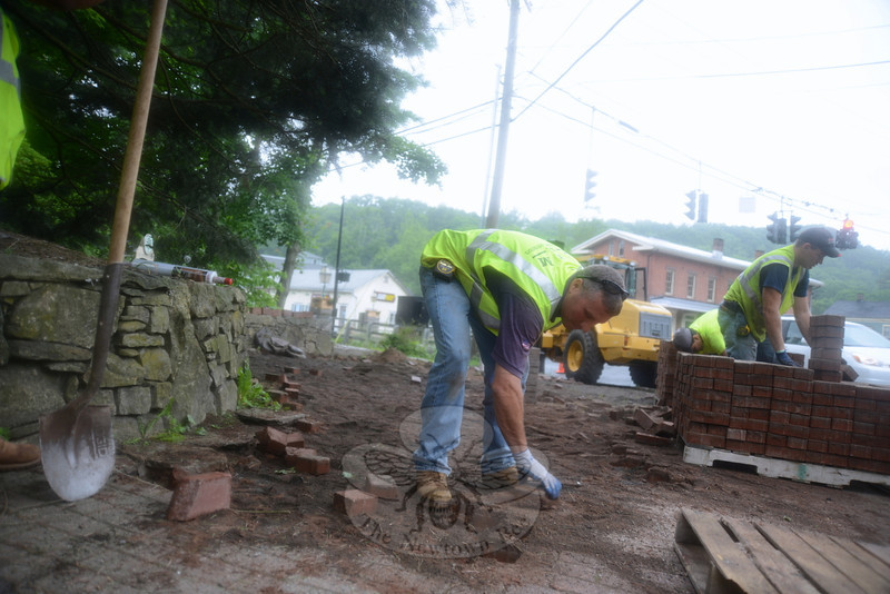 Rob Manna lifts old bricks from the walkway at The Glen in Sandy Hook Center. A new stamped concrete sidewalk will soon be in place.   (Bobowick photo)