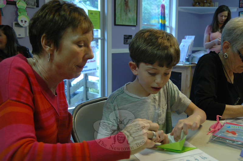 Max Dimeglio, 10, created an origami crane at the Sandy Hook Arts Center for Kids (SHACK) on Fri-day, June 7, with Pam Harmata, left, overseeing his creation. Paper cranes, yellow Pikachus, and other forms of origami also arrived at the SHACK, at 100 Church Hill Road, on Friday, June 7, from Japan, mostly made in the city of Kobe. Hisakazu Okamura delivered the creations with words of support from Japan. Colin Harrison organized the delivery and event.  (Hallabeck photo)