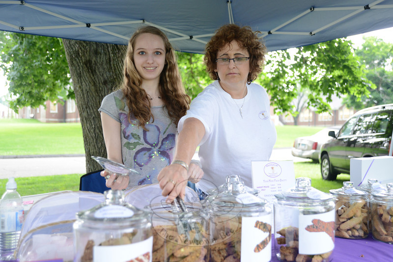 Jesse Plouffe, left, and Stephanie Schneiderman with Biscotti Etc LLC of Sandy Hook, display a host of flavors in cookie jars June 18, for the season's first Farmers Market at Fairfield Hills. (Bobowick photo)