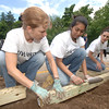 Members of a Newtown Savings Bank team volunteering for the United Way's Day of Action included, from left, Anita Schaub, Disha Damania, and Carla Begglo, who cleared out a garden bad and inserted wooden bed borders at The Children's Adventure Center.   —Bee Photo, Bobowick