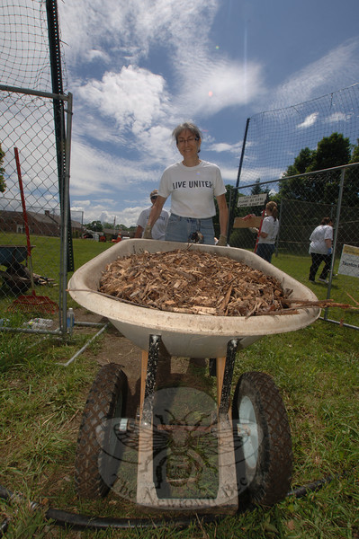 Nancy Boudreau wheels in a load of mulch to line paths between garden rows Wednesday.   —Bee Photo, Bobowick