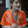 James Flechner, Jr, 11, the son of Bee Publishing employee Eileen Hardman, displays the medals he earned at the Southern Connecticut State University Special Olympics event held Friday, June 8. Swimming for Team Shelton, James won a gold medal for the 15-meter race, and a silver for the 25-meter freestyle relay. 	              —Bee Photo, Crevier