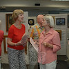 Society of Creative Arts of Newtown (SCAN), Inc. member Marianne Scanlon, left, speaks with artist Janice Papayani during last weekend's opening reception for the SCAN Spring Juried Art Show at C.H. Booth Library. The exhibit will remain on view during regular library hours until Saturday, June 16.   —Bee Photo, Bobowick