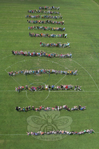 "Hawley School celebrated an all-day Math Day on June 5. Students completed a variety of activities in their classrooms involving math skills and concepts before heading out to the school's back fields to make a pictograph of birthdays celebrated in each month. With the field having 12 lines to choose from, students stood on the line that represented their birthday month. The photo was originally planned so that it would look like viewers were looking at an abacus, which reads like a book, from left to right, said Hawley School Lead Teacher Chris Breyan. When it was time to take the photo — which was done from the top of Hook & Ladder Fire Company's ladder truck — everyone needed to shift to the right, however. January is represented by the line (or rod) at the bottom of this photo; December is the uppermost rod. It is a close call, but the results look like this: April's rod has 40 students, but one staff member, giving the month 41 ""beads,"" while March has 39 students, but another six staff members, for a final tally of 45 birthdays marked.          —Bee Photo, Hicks"