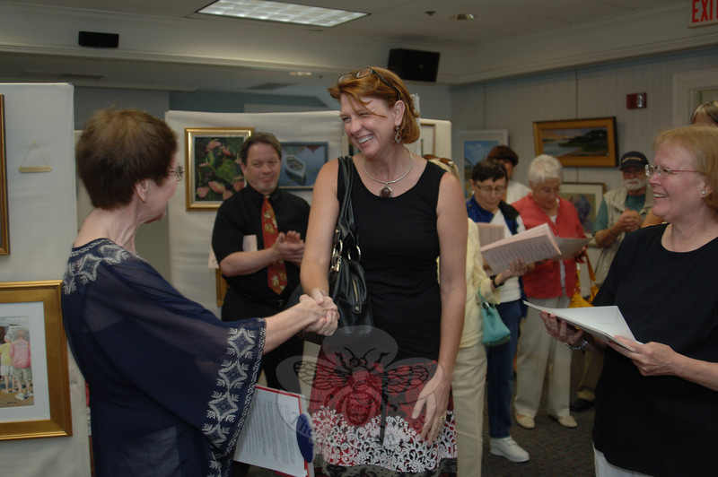 DeAnn Prosia, right, shakes hands with art show chair Pam Danneman after being named The Taunton Press Award winner during the June 10 opening reception of The SCAN Spring Juried Exhibition.	   —Bee Photo, Bobowick