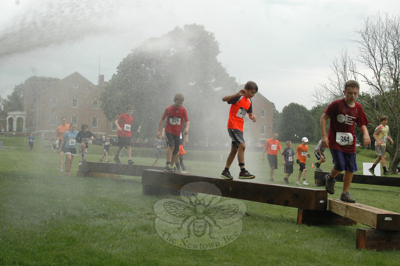 The Mad Dash debuted June 9 at Fairfield Hills, hosted by Newtown Youth Academy and the Newtown Parks & Recreation Department. Hundreds of adults and children traversed tunnels, hay bales, a mud pit and balance beams while being doused by water hoses handled by Newtown Hook & Ladder volunteers. Here, from left, Isabella Kaiser, Danny Arneth, Logan Sullivan, Conor Moran, Ben Drew, and William Swierbut endure the disorienting spray. —Bee Photo, Voket
