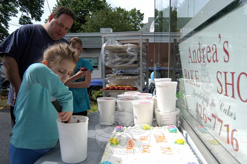 Michaela Shovak, left, was the first person to decorate a cupcake during a Customer Appreciation Day held at Andrea's Bake Shop on Sunday, June 3. Behind her in line were her father, Peter, and sister, Arianna.        —Bee Photo, Hallabeck