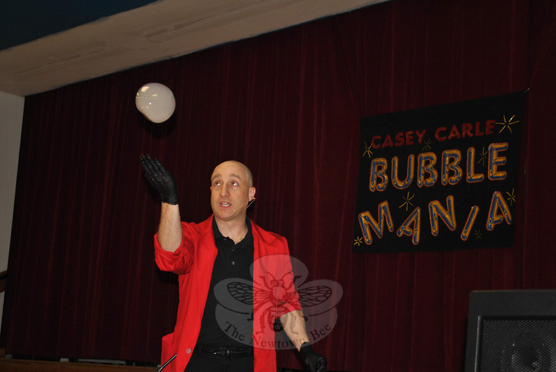 """Bubble expert Casey Carle shows off a nature-defying cubical bubble, filled with fog, Thursday, May 24, during """"BubbleMania!""""  at Head O' Meadow School.   —Bee Photo, Crevier"""