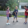 Looking forward to the first day of fifth grade on Wednesday morning is Lindsey Sherman, left. Ben Terry, a fifth grader to be, jokes with rising sixth grader Steven Moccio, right, at the bus stop.  (Crevier photo)