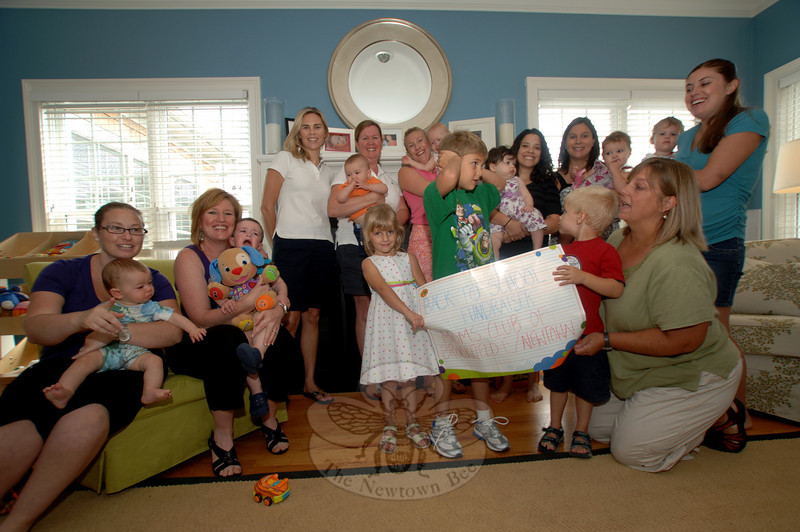 From left are MOMS members Amanda Carlin, Sheila Longhi, Tracey Trado, Diane Costallos, Sandra Camp, who hosted the event, Jessica Sachs, Shari Wright, Heather Symes, and Debbie Brooks. Children — several in diapers — offered a mix of emotions as moms held them still for a photo.  (Bobowick photo)