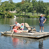 Cristina Lynders dabbles her fingers in Taunton Lake to amuse 18-month-old Kathryn, while Rob Lynders steers the motorized dock. Bill Lynders, far right, is a frequent passenger aboard the novel lake vehicle that son Rob created this past spring.  (Crevier photo)
