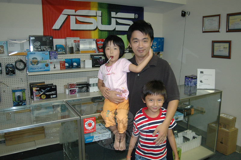 Paul Wang, proprietor of PC Warehouse on South Main Street, takes a break from work to enjoy a few minutes with his children, Andrew, 6, and Janna, 5. The local repair and retail shop boasts a customized pay-by-the-job pricing policy to help clients determine and budget for whether they need to repair or replace an ailing PC or Mac.  (Voket photo)