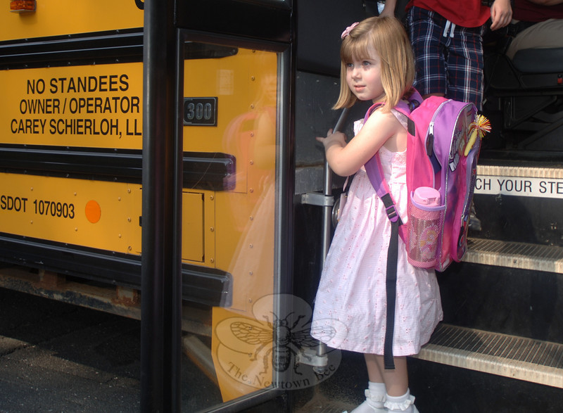 Returning from from her first day of kindergarten, Kaitlin Dole looked for her mother in the crowd at the bus stop.  (Bobowick photo)