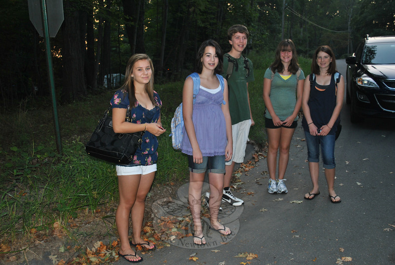 From left, middle school and high school students Brooke Pisacich, Veronica Eames, Patrick Pierce, Kaitlyn Pierce, and Hannah Godbout wait in the early morning light for the school bus that will take them to their first day of the 2010 school year.  (Crevier photo)
