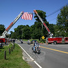 Members of Newtown Hook & Ladder and Sandy Hook Fire & Rescue coordinated their efforts for the 2010 CT United Ride by using their ladder trucks to raise a 12 by 18-foot flag over South Main Street on Sunday, August 29. A small group of friends and residents gathered along both sides of South Main Street with the firefighters, raising smaller flags and waving toward the estimated 2,500 motorcyclists as they passed under the flag.  (Hicks photo)