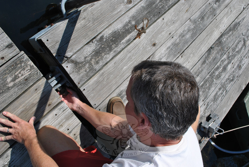 Oversized bolts secure the motorized dock to the gangway. Here, Rob Lynders easily unscrews the bolts before setting out.  (Crevier photo)