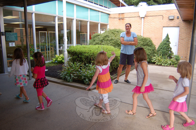 Jacky Hegarty waved to her mother Beth Hegarty at Sandy Hook School on Thursday, August 26, after she rode the bus for the first time. Jacky and her sisters, Shannon and Meghan, all visited the school as kindergarten students on Thursday.  (Hallabeck photo)