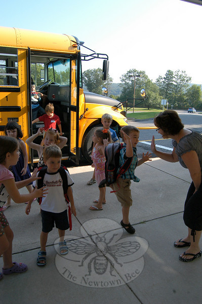 Middle Gate PTA President Lisa Wallace received a high five from a kindergartener as buses arrived bringing the kindergarten students to the school for the first time on Tuesday, August 31, for a preschool visit.  (Hallabeck photo)