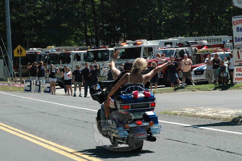 Two people riding on a motorcycle wave to onlookers standing near a row of Dodgingtown and Hawleyville fire trucks positioned in front of the Dodgingtown Firehouse during the CT United Ride.  (Gorosko photo)