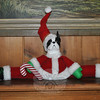 "A Boston terrier disguised as Santa's helper does the splits. A new product for 2010, Ms Adams' ""draft dodger"" is designed to sit snugly at the base of a door, but can serve a decorative purpose, too. The busts of any of more than 150 AKC recognized breeds can be affixed to the ""draft dodger.""  (Crevier photo)"