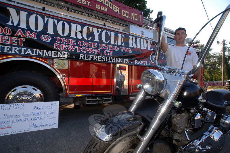 Tim Hoeffel rests against the handlebars after setting the banner in place advertising a motorcycle ride and fundraising event in mid-September.  (Bobowick photo)
