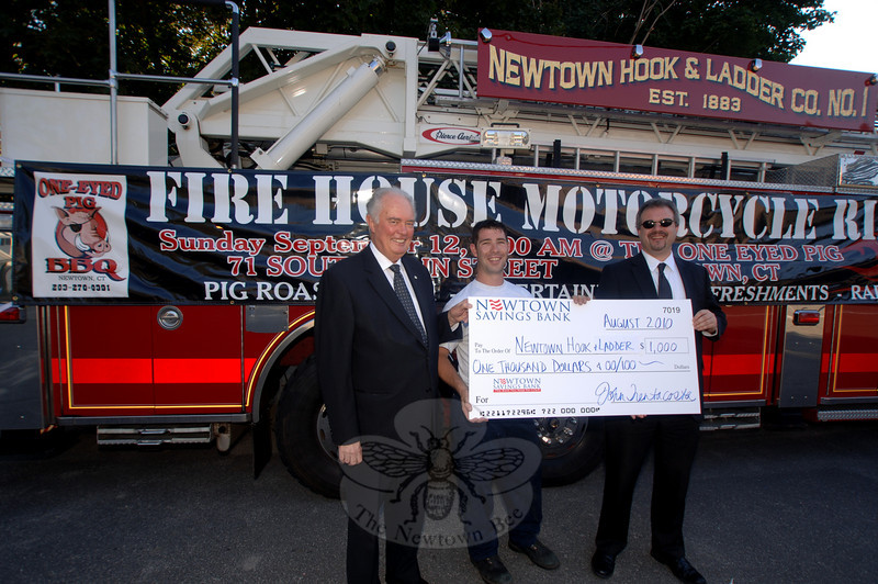 Presenting a check to support the Newtown Hook & Ladder Fire Company, Inc, No. 1's upcoming September 12 firehouse fundraiser pig roast and motorcycle ride are Newtown Savings Bank Assistant Vice President Brian Amey, left, and Assistant Manager Ryan Storms. Receiving their Platinum donation of $1,000 is company firefighter Tim Hoeffel.  (Bobowick photo)