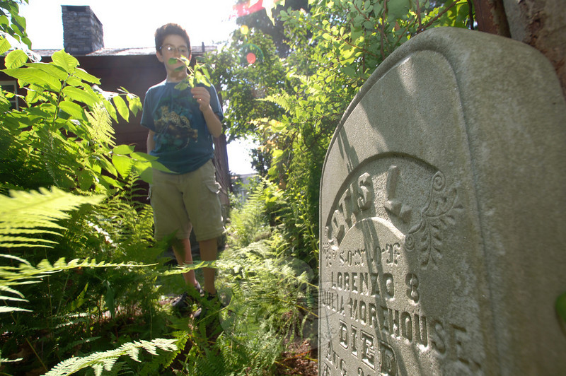 Junior docent Ian Villamil reveals a hidden headstone that had been dropped off at the house without a clue to who left it there. The stone marks the death of Julia Morehouse in August 1864.  (Bobowick photo)