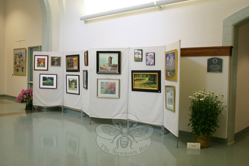 """Newtown Images, New England Charm"" offers 100 original works of art by members of The Society of Creative Arts of Newtown (SCAN) in the main hallway of Newtown Municipal Center. A small portion of the collection can be seen here during the show's opening reception.  (Hicks photo)"
