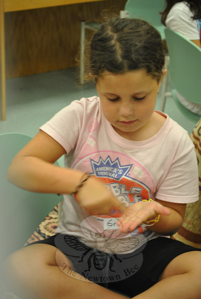 "Grace Howgego rubs some oil into the palm of her hand. Participants in the ""Water Wizards"" program on Tuesday, July 20, learned how difficult it is to clean oil off of surfaces or remove it from water.  (Crevier photo)"