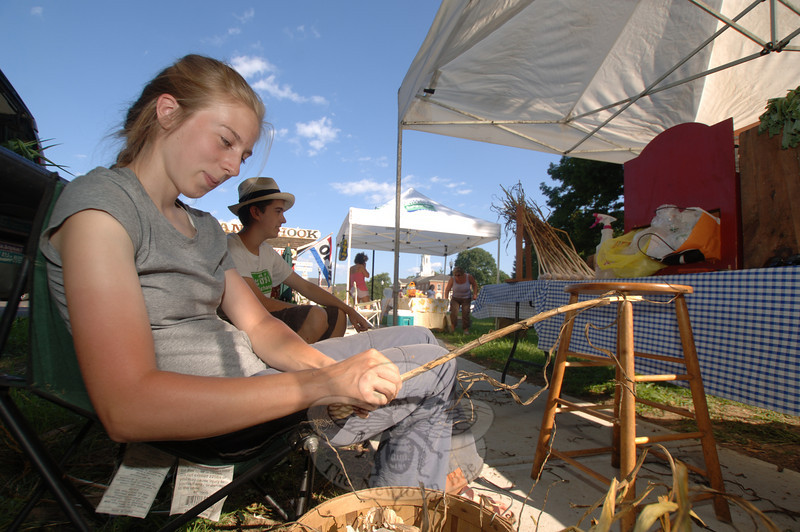 Jacqueline DeWitt cleans garlic stalks and bulbs and prepares them for sale Tuesday, July 27, at Sandy Hook Organic Farmers Market.  (Bobowick photo)