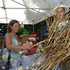 Alison Satran of Sandy Hook shops at the Sandy Hook Organic Farmer's Market set up in Fairfield Hills Tuesday, where she selected garlic bulbs, still attached to the stalks. The produce comes from Warrups Farm in Redding. Behind the garlic is Lincoln Hill, helping Alison with the selection.  (Bobowick photo)
