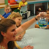 "Sabrina and John Boccuzzi look on as Bonnie Shugrue shows them how oil and corn syrup separate from water during an experiment on density at the July 20 ""Water Wizards"" program.  (Crevier photo)"