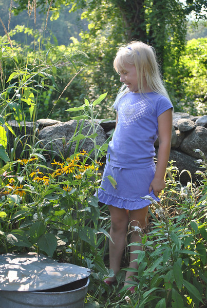 Joining in on a family tradition of gardening, Melinda Ferris shows off the sunflower she has grown from a bag of birdseed this summer.  (Crevier photo)