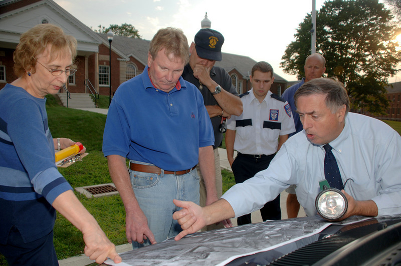 Perusing building locations on a map are Fairfield Hills Master Plan Review Committee members, from left, Nancy Roznicki, Bob Maurer, Steven zVon, campus security officer Richard Gagne, committee member Michael Mossbarger, and Public Works Director Fred Hurley. Additional committee members soon arrived Monday, August 2, for a building tour beginning shortly after 7 pm.  (Bobowick photo)