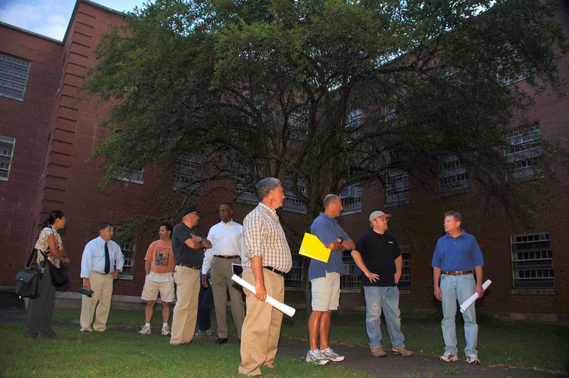 Fairfield Hills Review Committee members wait for security officer Richard Gagne to unlock Cochran House during their campus tour this week.  (Bobowick photo)