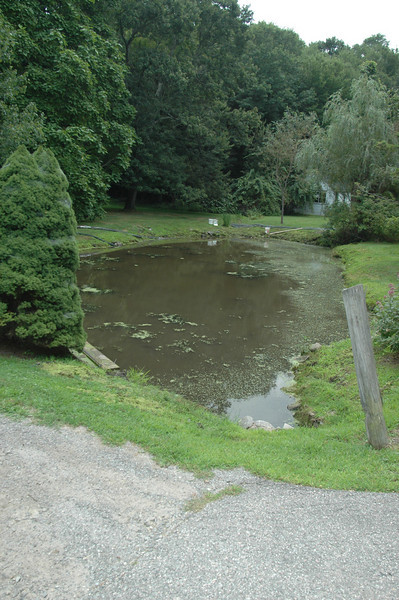 Side-by-side ponds in the Hattertown Historic District illustrate a before (previous photo) and after effect (this photo) following the removal of duck meal from the surface of one of the water bodies. A crew from Newtown-based Aquamarine Environmental Solutions is currently working in stages to first remove surface growth on both ponds before going underwater to clear weeds and debris.  (Voket photo)