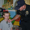 "Newtown Police Officer Jason Flynn ""deputized"" Tumble Jungle camper John O'Sullivan, following a Q&A session on what a police officer does. Officer Flynn was at Tumble Jungle on August 6 for ""Hometown Heroes Camp,"" a salute to Newtown's safety officers, and a fun way for kids ages 3-8 to learn about safety and emergency personnel, said camp director Kim Nezvesky. The weeklong camp featured games and relay races related to heroes. Other visitors to the camp during the week were members of Botsford Fire Rescue, Newtown Vol-unteer Ambulance Corps, and school bus driver Maria Adams, along with transportation members Cathy Hydeck and Maritza Nezvesky.  (Crevier photo)"