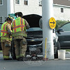 Newtown Hook & Ladder firefighters checked under the hood of a 2010 Chevrolet SUV that was involved in a one-vehicle accident at the Main Street flagpole about 9:30 am August 20. Police said motorist Karan Moseman, 65, of Yorktown Heights, N.Y., was driving the Chevrolet westward on Church Hill Road, after which she attempted to turn left onto southbound Main Street. While attempting the turn, the vehicle collided with the Main Street flagpole. Moseman told police that she was uninjured, but she was evaluated by ambulance staffers and then transported to Danbury Hospital to be checked. Moseman received a written warning for making a restricted turn.  (Gorosko photo)