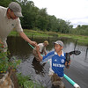 On August 23 Dan Holmes, background, stands thigh-deep in the Newtown Forest Associa-tion property at Cavanaugh Pond off Echo Valley Road where he constructed a beaver ex-closure with help from Bolivar Pacheco, also in the water, and Marcial Manendez, standing on the shore. The Newtown Forest Association consulted site engineers Amy S. Greene En-vironmental Consultants, Inc, which specialize in these issues.  (Bobowick photo)