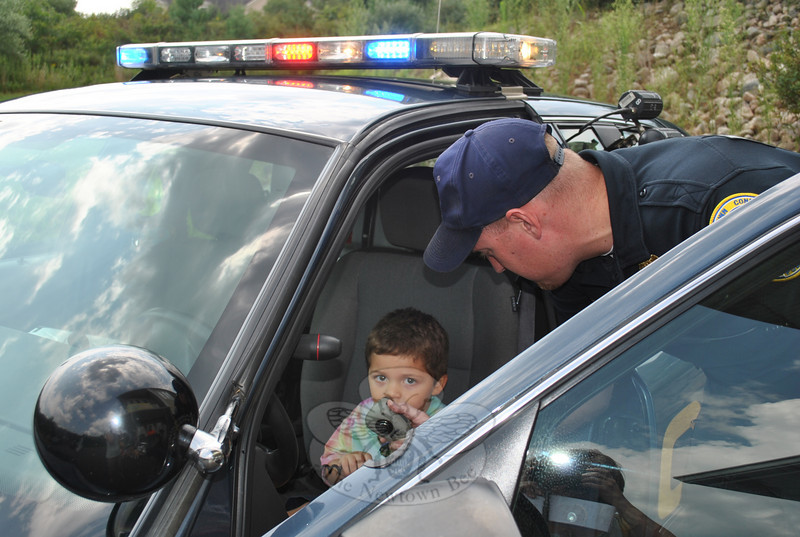 "Evan Deleo gives a ""shout out"" on the police radio as he sits in the front seat of a Newtown PD cruiser while Officer Jason Flynn looks on. Officer Flynn was at Tumble Jungle on Au-gust 6 for ""Hometown Heroes Camp,"" a salute to Newtown's safety officers, and a fun way for kids ages 3-8 to learn about safety and emergency personnel, said camp director Kim Nezvesky. The weeklong camp featured games and relay races related to heroes. Other visi-tors to the camp during the week were members of Botsford Fire Rescue, Newtown Volun-teer Ambulance Corps, and school bus driver Maria Adams, along with transportation members Cathy Hydeck and Maritza Nezvesky.  (Crevier photo)"