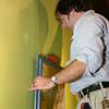 """Sandy Hook resident Adam Zuckerman has been curating the exhibitions at The Blue Z Coffee House for over a year. One of the space's biggest challenges, he says, is this green wall. """"This one has to be filled first. This green does not get along with a lot of art,"""" said Mr Zuckerman.  (Hicks photo)"""