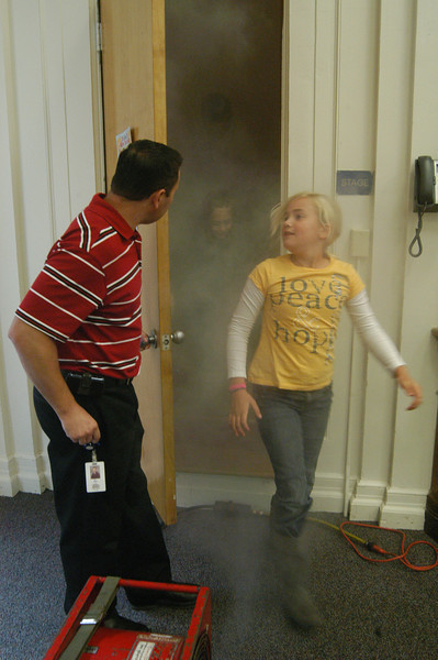"""Hawley Elementary School fourth grade student Carolina Stubbs was one of many students who crawled through a temporary """"smoke room"""" set up on the stage of the school's multi-purpose room on Tuesday, October 5. Fourth grade teacher Michael Wight welcomed Carolina and her fellow students out of the smoke room for the event, which was part of the school's observation of October 3–9 as National Fire Prevention Week. Chris Gindraux and Ricky Camejo of Newtown Hook & Ladder oversaw the smoke room after explaining fire prevention tips to the students. (Hallabeck photo)"""