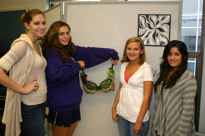 "Thirteen members of Diane Dutchick's Art Portfolio I class at Newtown High School signed on to be ""bratistas,"" the artists responsible for creating elaborately decorated bras for ""Perfect Pairs: The Artful Bra Show."" From left is Paige Olson, Katherine Scott (holding her creation, which incorporates plastic grapes, grapevine, corks, and what appears to be an Italian countryside scene), Emily Kopcik and Dominique Allen. The students, according to Mrs Dutchick, had less than three weeks to design and decorate their bras, but each came up with brilliant results, all of which will be sold through silent auction on October 23.  (Hicks photo)"
