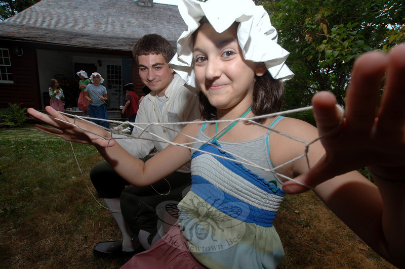 Stretching out her string forming Jacob's Ladder, Sophia Patelli smiles as Brandon Weiner looks at the shapes she has knit with her fingers.  (Bobowick photo)