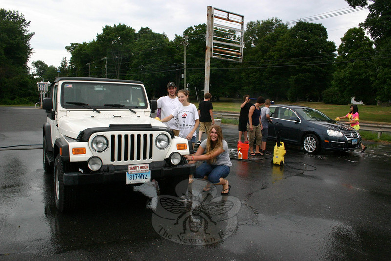 What's a little rain when you're going to spend hours outside washing cars anyway? That was the positive attitude held by the members of Grace Christian Fellowship's youth group preparing for a trip later this month to Costa Rica, who volunteered part of their weekend to wash cars. The group's final fundraiser before they head to Central America was a car wash conducted at Amaral Motors on Saturday, July 10. For six hours the young adults washed cars — sometimes while it was raining and the owners stayed inside their vehicles — in exchange for donations. Among those participating on Saturday were, at the Jeep, from left, Michael Barago and Abbie Bruno of Newtown and Jessica Reardon of Naugatuck. GCF Youth & Children's Pastor Adam Fredericks said 24 members of his church (20 young adults and four adult chaperones) will be going on the trip, when they will be among a number of groups working through Samaritan's Church to help build a church, among other scheduled activities, during their stay.  (Hicks photo)