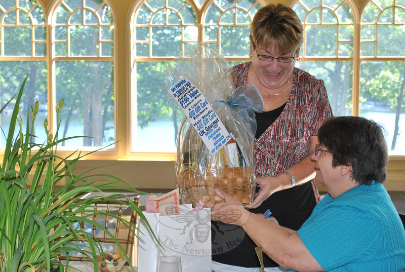 Hospice breakfast volunteer Colleen Honan hands Marion Thompson her second raffle prize of the morning. Ms Thompson won a gift certificate to the June 11 Art of Caring event, and a gift basket donated by Taunton Wine, UK Gourmet and Klickers Hair Studio.  (Crevier photo)