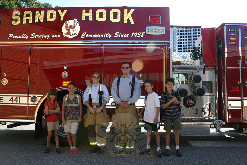 Four students who attend Sandy Hook School had a very special ride to school Tuesday morning. James and Julia Doyle and Garrett and Madison Fetchick were picked up at the Doyle home on June 8 and driven to school in Sandy Hook Fire & Rescue Company's brand-new 2010 Pierce Engine. The children were driven in by Lieutenant John Jeltema and EMS Captain Karin Halstead, thanks to a winning bid by the children's parents during the Sandy Hook School PTA Spring Auction. Stacie and James Doyle and Kathy and Jeff Fetchick secured the special event for their children when they were the top bidders for the lot on March 13. From left are Madison, Julia, EMS Capt Halstead, Lt Jeltema, James and Garrett.  (Hicks photo)