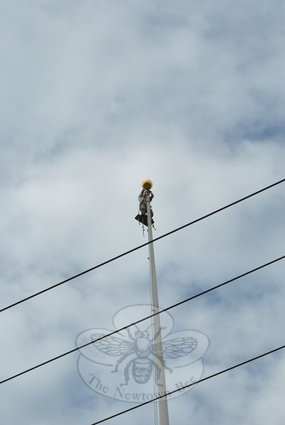 Paul Bastiaanse affixes the 16-inch diameter golden ball to the top of the flagpole Wednesday morning, June 9. His company, Valley Restoration of Torrington, had removed the ball on Monday for regilding.  (Crevier photo)