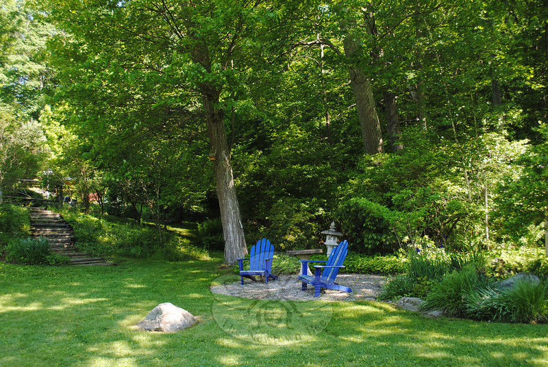 Lush foliage and irises surround Adirondack chairs in this restful garden on Howard Lasher's property. A rustic staircase to the left leads to a pool and still more gardens.  (Crevier photo)