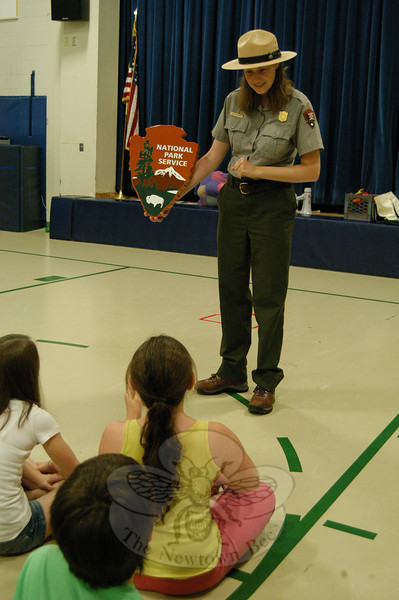 Weir Farm National Historic Site Park Ranger Emily Bryant held up the National Park sign on Friday, June 4, in Hawley Elementary School's gymnasium to start her presentation on national parks for fourth grade students during an enrichment block at the school.  (Hallabeck photo)